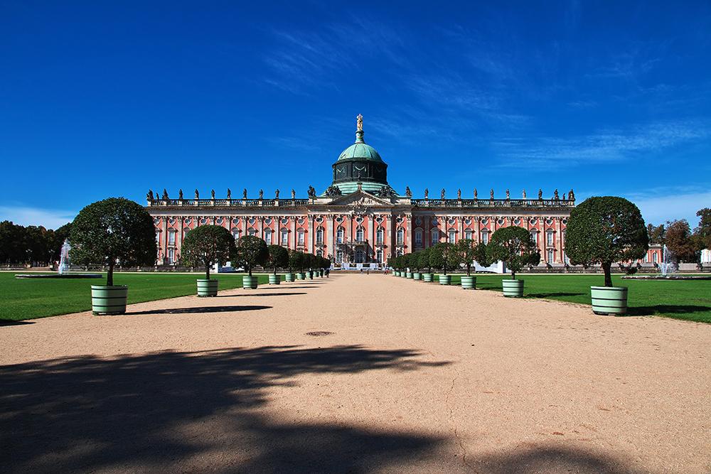 Das Neue Palais in Potsdam leuchtet melonefarben zwischen grünen Gärten und einem blauen HImmel.