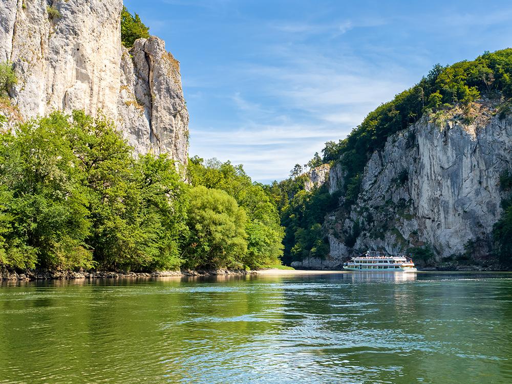Ein Ausflugsschiff fährt zwischen Kalsteinfelsen auf der Donau Richtung Kloster Weltenburg.