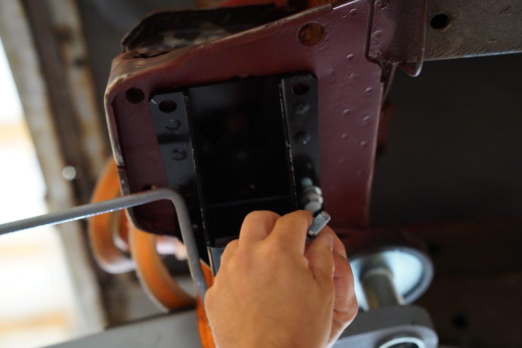 Die neue Halteplatte für die vordere Blattfederaufnahme am Fiat Ducato Maxi 290 wird mit der ersten von vier Schrauben befestigt.