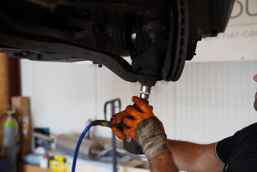 Nahaufnahme der Bremsscheibe samt Traggelenk und eingerissener Gelenkmanschette beim Ducato 250, eine Schraube des Traggelenks wird mit einem Schlagschrauber gelöst.