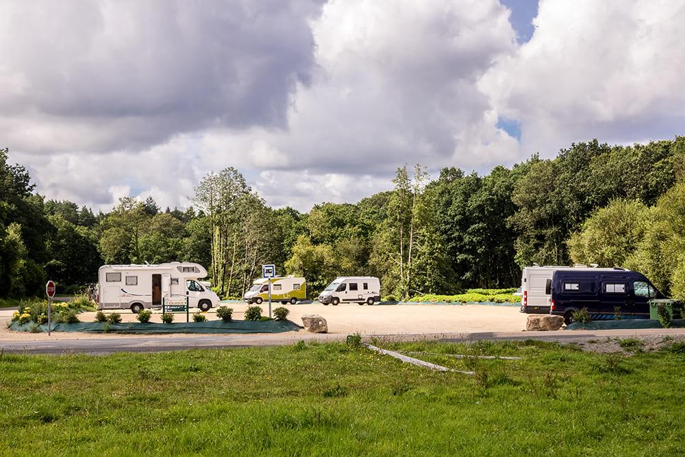 Ein Wohnmobilparkplatz mitten im Grünen zwischen Wiesen und Bäumen.