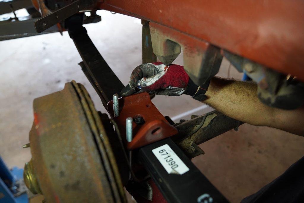 Die entrostete und mit Rostschutz versehen Blattfederhalterung wird in Position gebracht und mit Schrauben versehen.