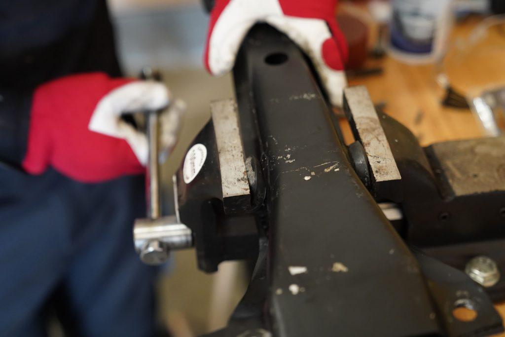 Die Silentbuchsen der hinteren Blattfederaufnahme werden mithilfe einer Schraubzwinge auf einer Werkbank in die Halterung gedrückt.
