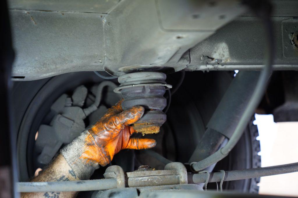 Das Hinterachsanschlaggummi an der Hinterachse eines Fiat Ducatos 250 wird nach dem Losklopfen per Hand losgedreht.
