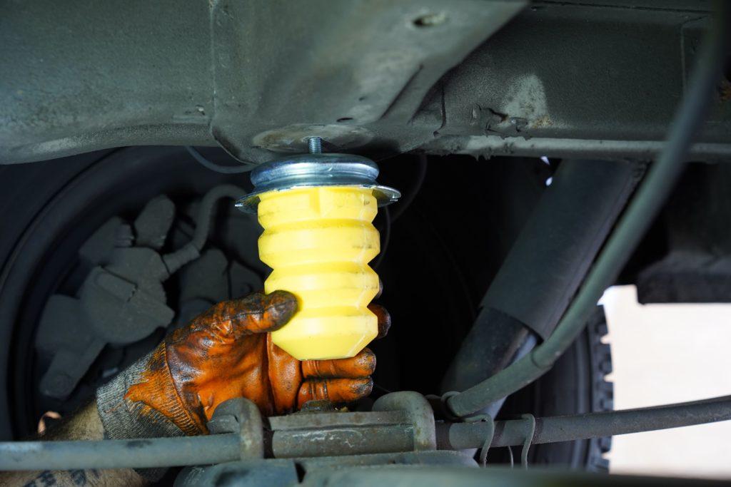 Das neue Hinterachsanschlaggummi an der Hinterachse eines Fiat Ducatos 250 wird per Hand festgedreht.
