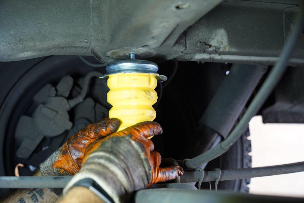 Das neue Hinterachsanschlaggummi an der Hinterachse eines Fiat Ducatos 250 wird mit zwei Händen festgedreht.