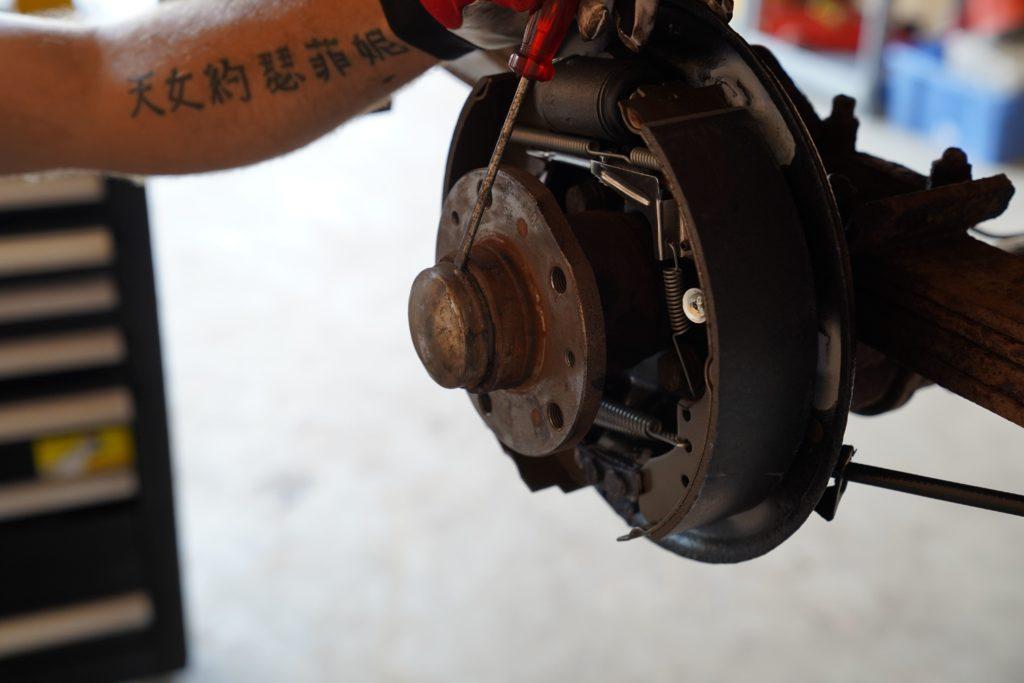 Die Fettkappe am Radlager wird mit einem Schraubendreher entfernt.