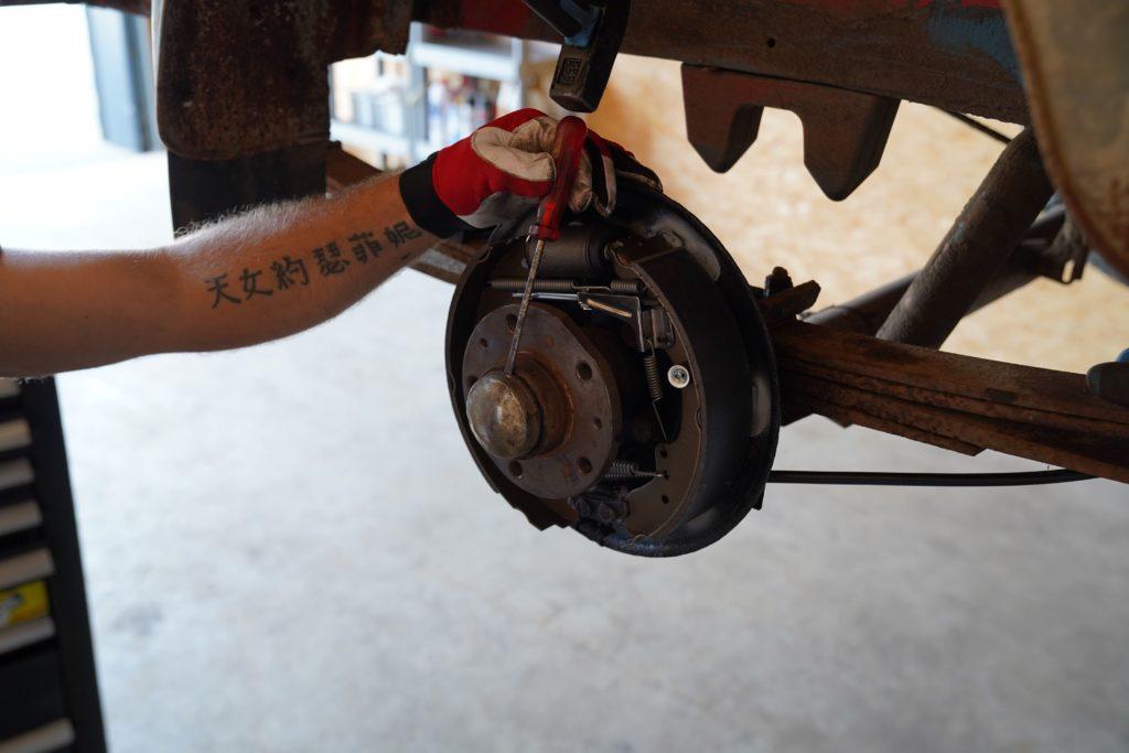 Die Fettkappe am Radlager wird mit einem Schraubendreher und einem Hammer entfernt.