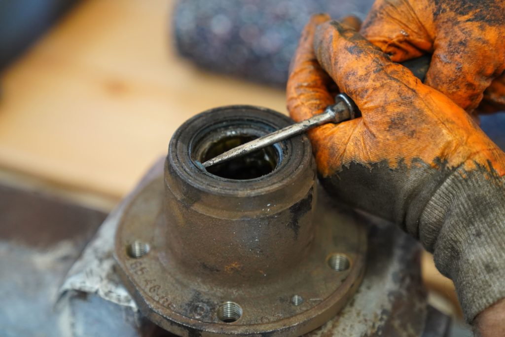 Die Radnabe in einen Spannstock eingespannt, mit einem Schraubendreher wird die Dichtung herausgedrückt.