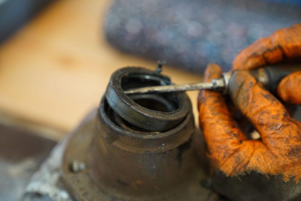 Die Radnabe in einen Spannstock eingespannt, mit einem Schraubendreher wird die Dichtung herausgedrückt, die schon fast komplett herausgedrückt ist.