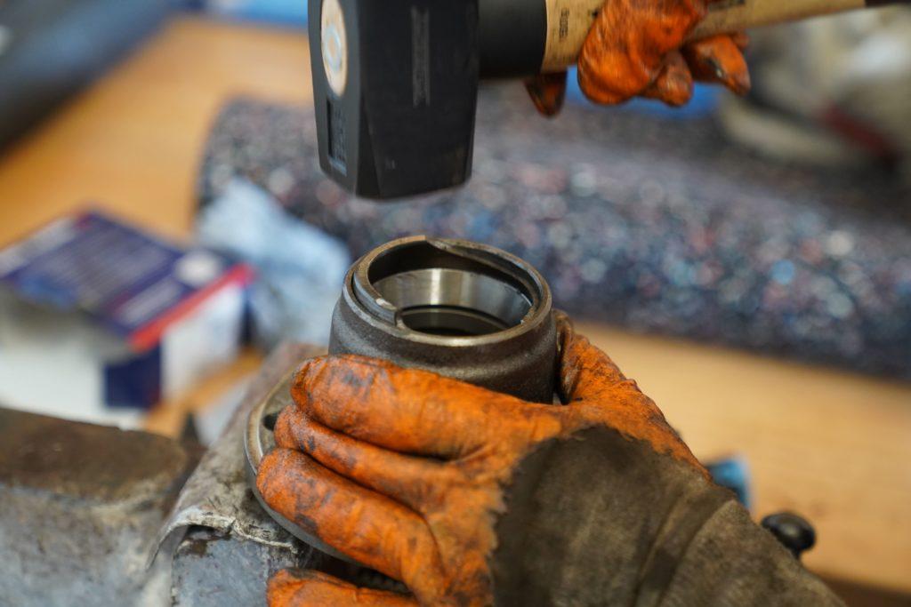 Die Radnabe in einen Spannstock eingespannt, die neue Lagerschelle wird mithilfe der alten Lagerschalle und eines Hammers vorsichtig in Position gehämmert.