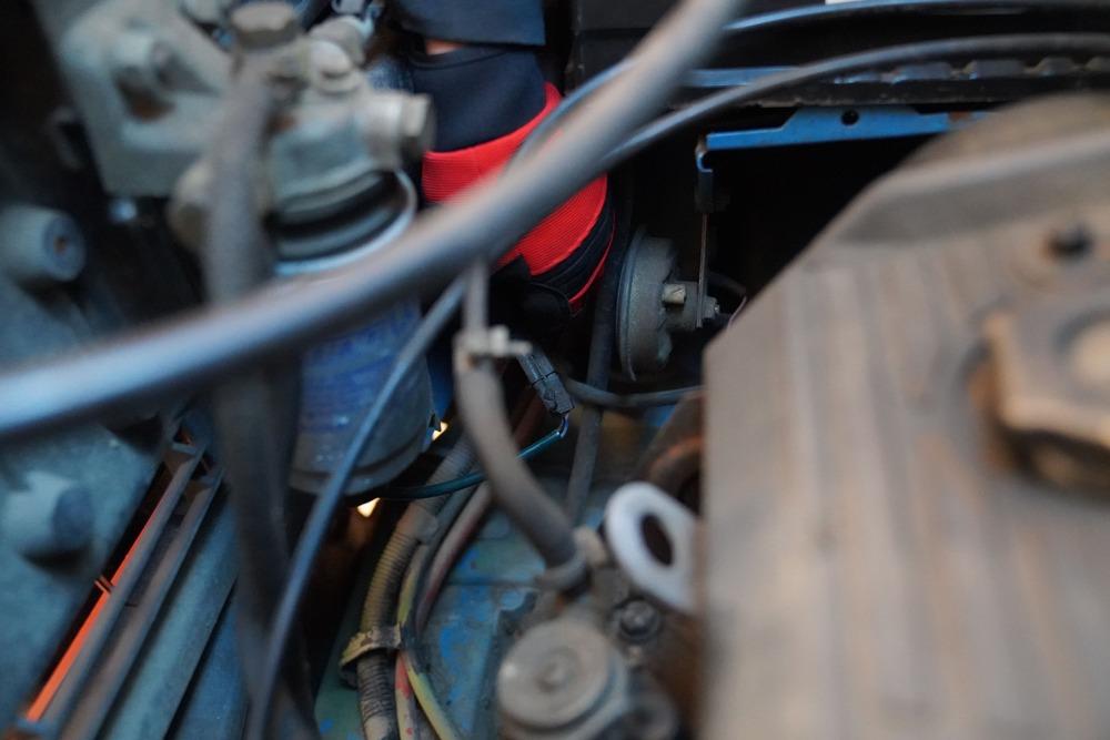 Mechaniker löst den Sensor eines Kraftstofffilters beim Ducato 290 im Motorraum.