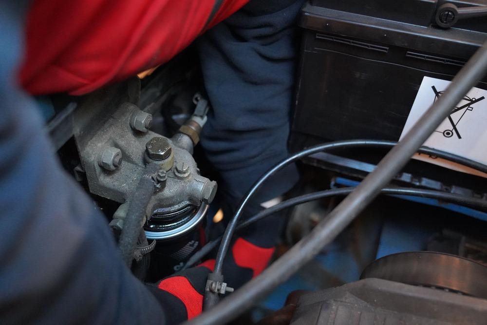 Ein Mechaniker dreht den neuen Kraftstofffilter im Motorraum eines Ducatos 290 mit circa 30 Nm fest.